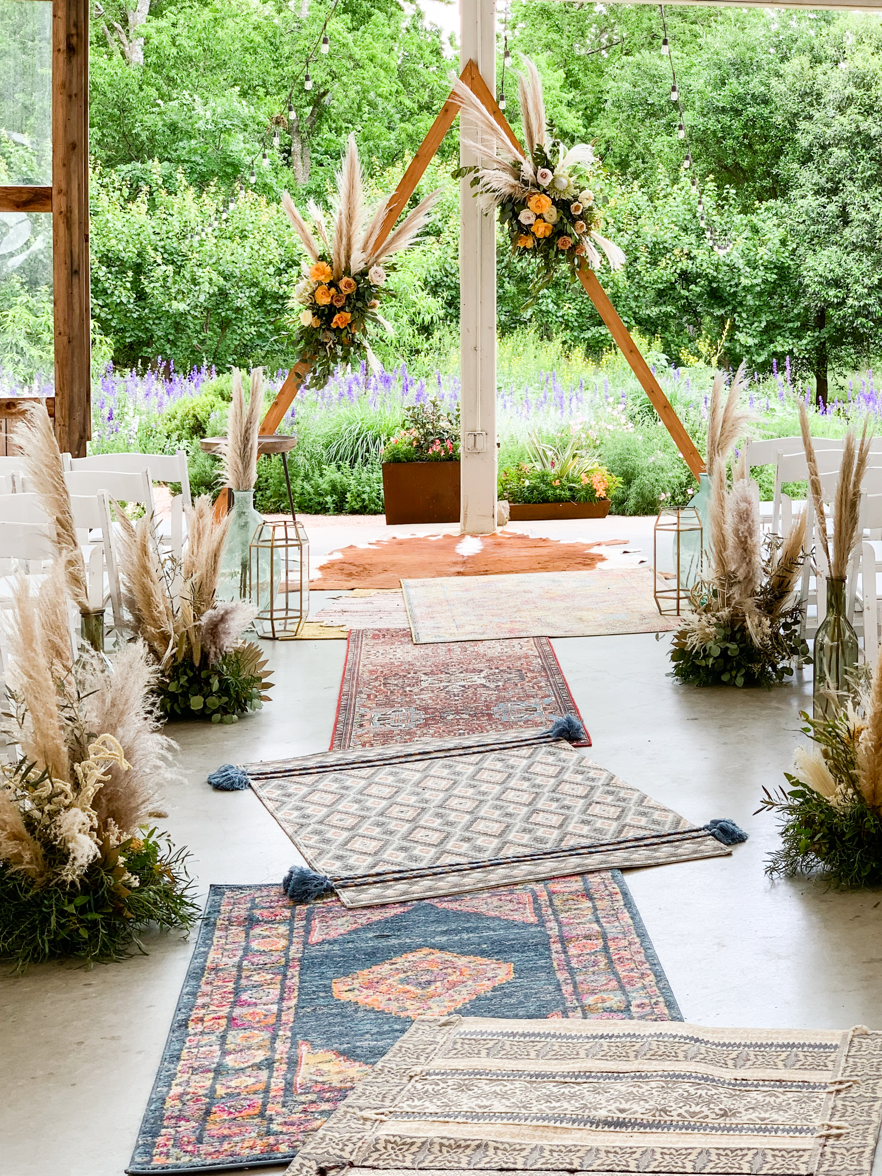 the wedding ceremony aisle was adorned with rugs and pampas grass arrangements